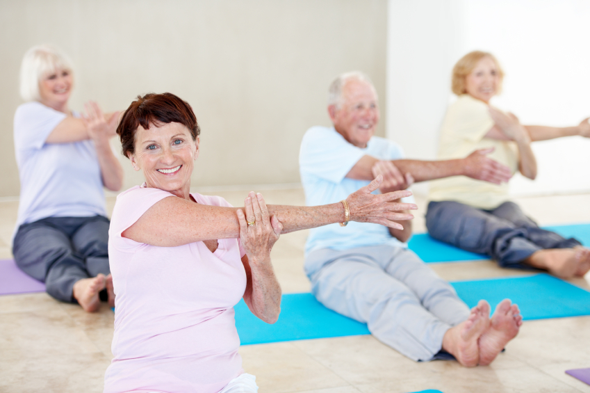 Portrait of a senior woman enjoying a yoga class with other seniors